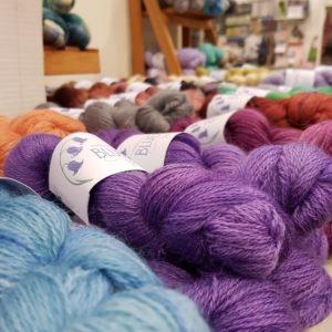 Wonderwool Stall - A closeup of some purple sock yarn with lots of other colours in the background.