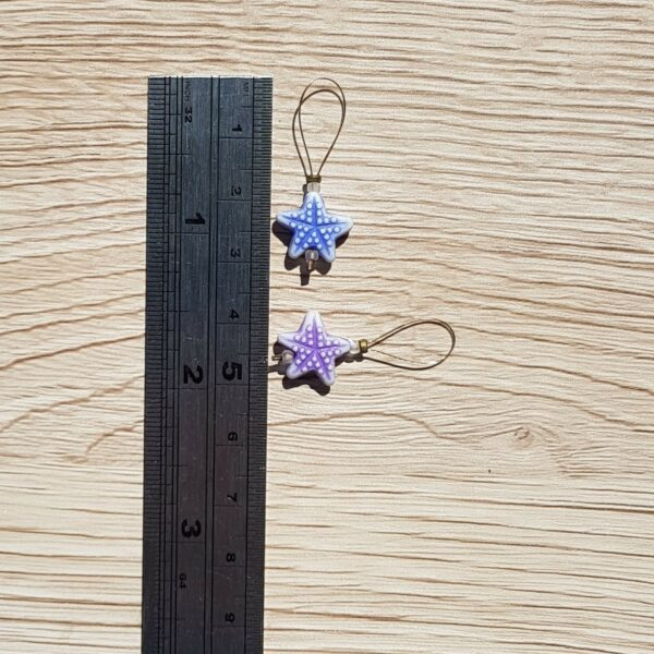 Starfish stitch markers against a ruler. Length approx. 3.5cm width approx 1.5cm