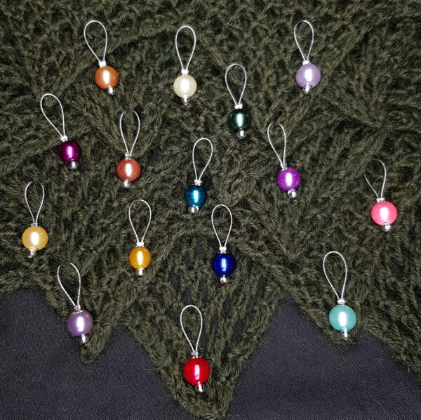 Glass bead stitch markers on a green lace knitted background