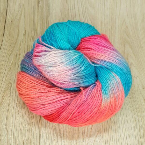 """Slushie"" a bright cyan-blue and orange-pink skein of yarn"