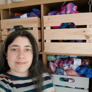Becca is stood in front of a shelving unit with crates full of multicoloured wool on it. She has shoulder-length dark brown hair with grey streaks and is smiling slightly.